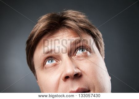 Close-up of adult man looking up with curiosity against of black background