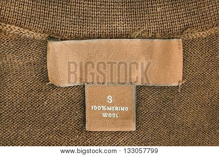 Fabric composition label on brown wool as a background