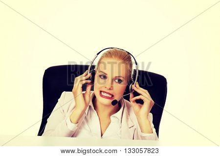 Young woman helpline operator is trying to hear something through a headphones