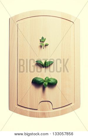 Leaves of lovage mint and basil on wooden board
