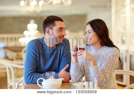 people, communication and dating concept - happy couple drinking tea at cafe or restaurant