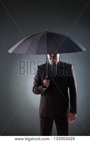 Portrait of unrecognizable man hiding face with umbrella.studio shot