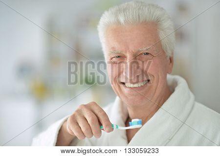 elderly man  brushing his teeth in bathroom