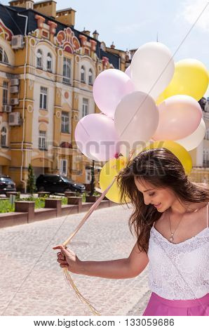 Girl with colorful latex balloons keeping her dress urban scene outdoors.