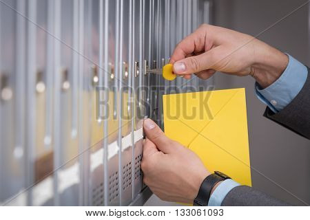 Man holding a yellow envelope, and locking the letterbox.