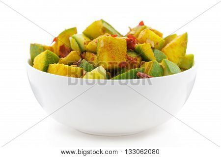 Organic sliced Indian Mango (Mangifera indica), seasoned with turmeric, salt and red chili pepper in white bowl. Isolated on white background. Front view.