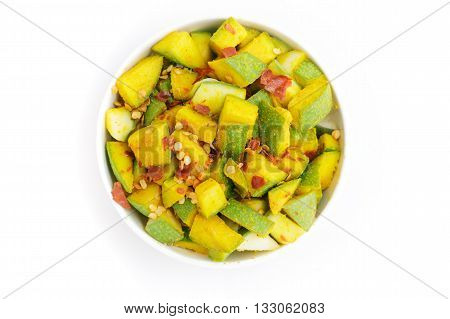 Organic sliced Indian Mango (Mangifera indica), seasoned with turmeric, salt and red chili pepper in white bowl. Isolated on white background.Top view.