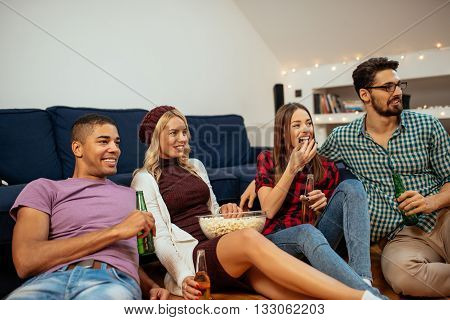Group of friends enjoying beer and pop corn at home.