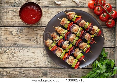 Traditional turkey or chicken meat skewers shish kebab with onion and tomatoes, parsley, ketchup in clay dish on rustic wooden table background. Barbecue grill food.