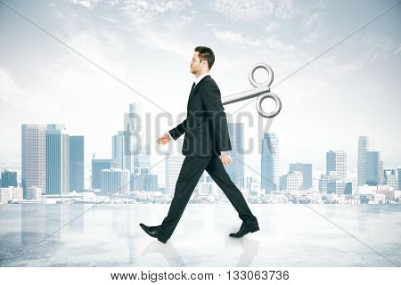 Walking businessman with a wind-up key on his back walking on abstract city background. Concept of control