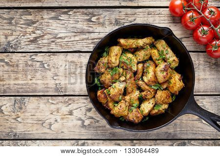 Fried sliced chicken or turkey fillet meat with chopped parsley and tomatoes on rustic wooden table background