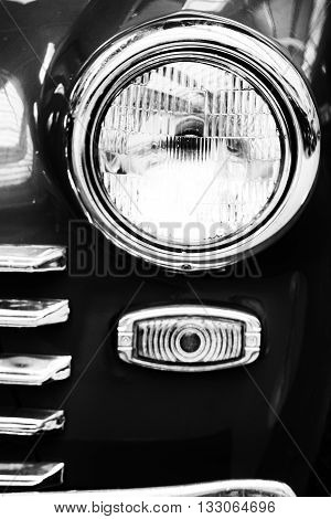 Retro car headlight close up photo. Right headlamp of old car black and white