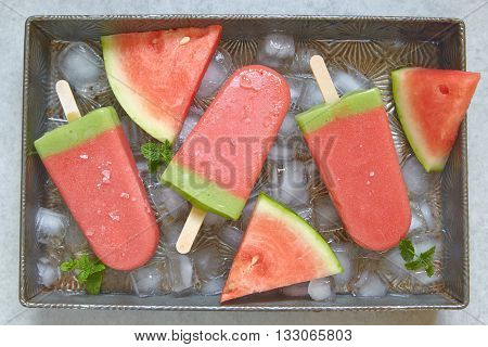 Watermelon popsicle with ice cubes on tray