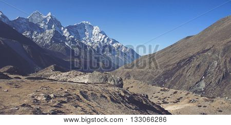 Silt in dry valley of Himalayan foothills with high mountain peaks covered in snow under panoramic blue sky