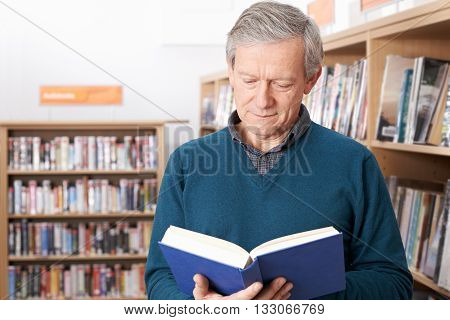 Mature Male Student Studying Book In Library