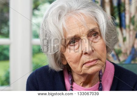 Head And Shoulders Portrait Of Thoughtful Senior Woman At Home