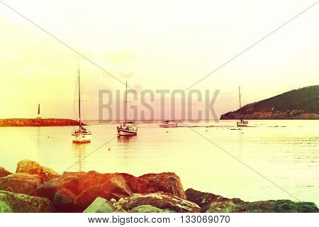 tranquil sea scene with anchored boats and lighthouse after the sunset.