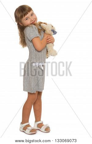 Cute little blonde girl pressed to his chest a stuffed toy - Isolated on white background