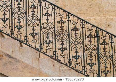 Part of the stairs from a side with visible rhythm of the steps and iron handrail with motive of compass and anchor. Stone wall in the background. Island Malta