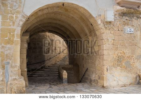 Fortification built in several levels in city Senglea mediterranean island Malta. Gate - underpass and stairs to the next floor.