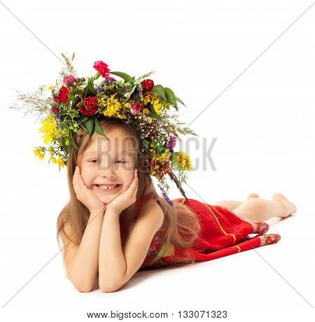 Cute little girl Ukrainian woman lies on the floor in a red dress and smiles . on the head the girl has a beautiful wreath of bright wildflowers - Isolated on white background