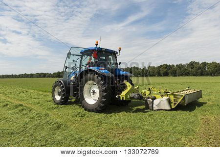 pasture mowing with blue tractor and mower