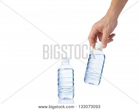 Male's hand grabs a bottle of water with another bottle of water on white table isolated white background with copyspace