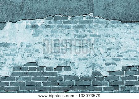 ancient texture of an old blue brick wall with destroyed plaster for background in vintage style and for old wallpaper