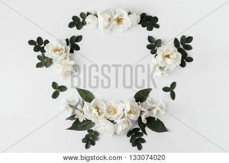 White wild roses and jasmine flowers frame with leaves on white isolated background copy space flat lay top view