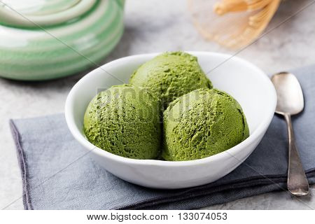 Green tea matcha ice cream scoop in white bowl on a grey stone background.
