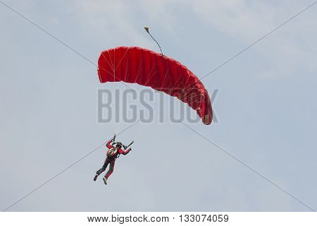 Parachutist floating to a square shaped parachute
