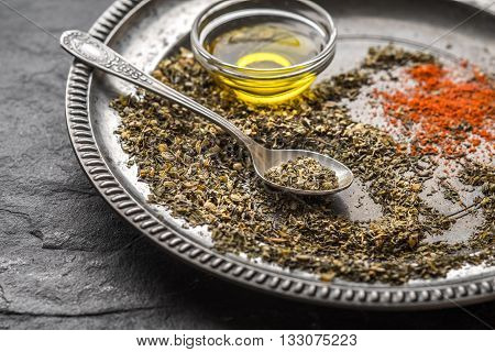 Spices for gyros paprika spoon oil tin plate on a black slate horizontal