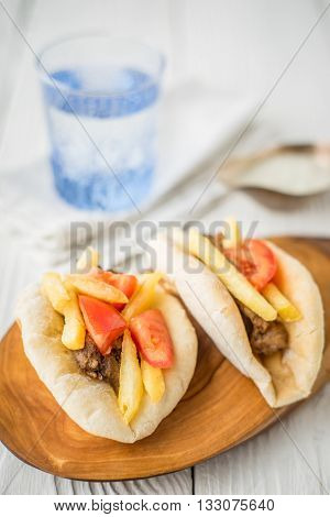 Gyros a glass of water dzatziki in a gravy boat on a wooden stand vertical