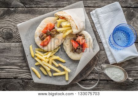 Gyros with potatoes meat pita bread and tomato on a glass of water on wet boards horizontal