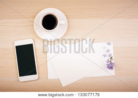 Top view of wooden desktop with blank smart phone screen empty card and coffee cup. Mock up