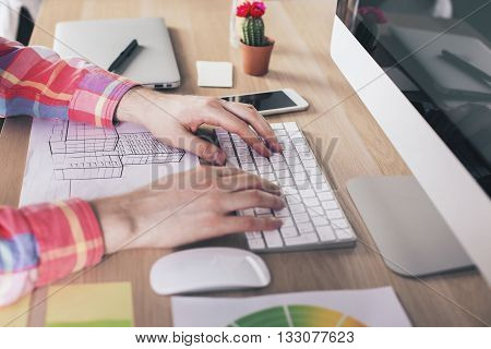 Side view of male hands using computer keyboard on wooden desktop with construction sketch computer monitor smart phone cactus and other items