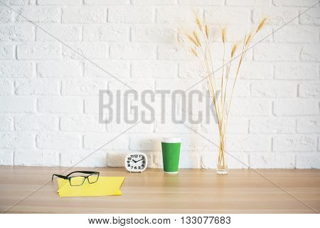 Front view of glasses yellow paper sheets clock green coffee cup and wheat spikes on wooden desktop and white brick background