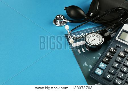 Medical manometer, calculator and medical record on blue background