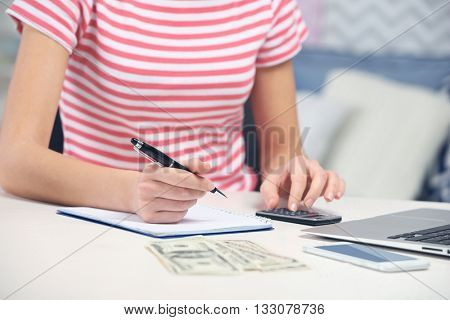Woman counting money and making calculations