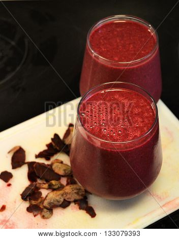Two beetroot smoothies on a cutting board with some beetroot flakes.