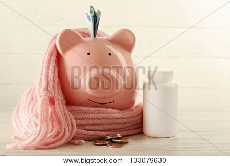 Piggy bank with scarf and pills. Health Insurance concept