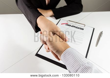 Top view of banker and customer handshake over the approved loan application document.