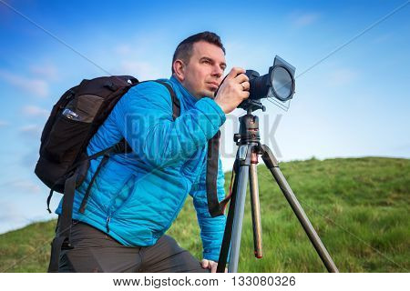 Landscape photographer with tripod over blue sky