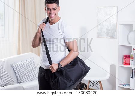 Handsome man with a sport bag standing at cozy home interior