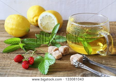 Mint tea in a glass cup with lemons and strawberry. Toned image. Focus selective