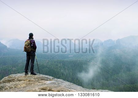 Hiker With Backpack And Poles On Cliff Rock  Watching Over The Misty And Foggy Spring Valley To Hori