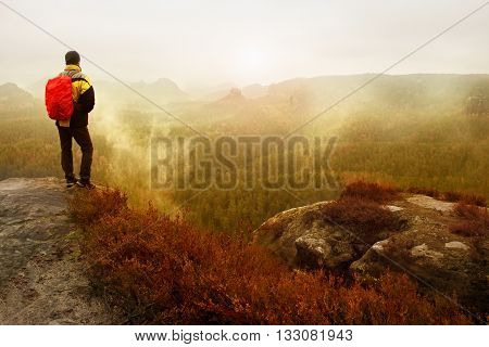 Rear View Of Male Hiker In Yellow Black Jacket, Daybreak After Rainy Night In Mountains