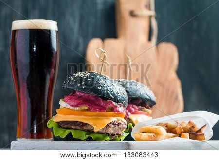 Homemade burger with black bun, beef meat and red berries sauce with glass of dark beer and French fries over wooden table with black background.