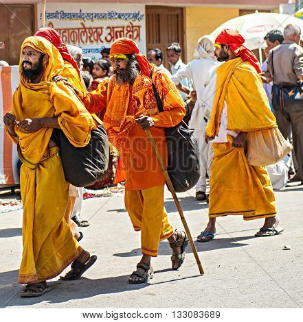 Ujjain, India - 21 April 2016: Pilgrims in traditional yellow and orange clothes walking at Kumbha Mela ground. Kumbh is a sacred event that is celebrated after every twelve years in India. It is one of the largest human gatherings in the world.