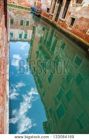 vintage colorful buildings reflected on water canal, in Venice. Focus on reflection in water
